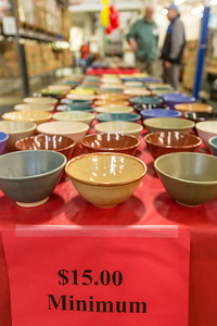 Ceramic bowls made by UAF art major Ian Wilkinson are laid out on tables at the Fairbanks Community Food Bank to be sold as part of his senior thesis project. All 1,200 individual bowls sold in about 30 minutes, raising about $18,000 donated to the local charity.  Filename: AAR-13-3790-5.jpg