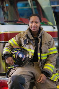 UAF student firefighter/EMTs Lillian Hampton poses by one of the firetrucks housed in the Whitaker Building on the Fairbanks campus.  Filename: AAR-11-3223-151.jpg