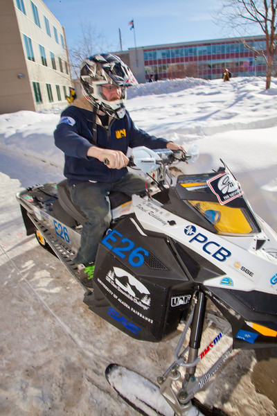 """Engineering major Isaac Thompson drives the electric snowmachine he and other members of his team helped modify into the Duckering Building after its return to campus after claiming the top prize in the SAE Clean Showmobile Challenge in Houghton, Mich.  <div class=""""ss-paypal-button"""">Filename: AAR-12-3337-52.jpg</div><div class=""""ss-paypal-button-end"""" style=""""""""></div>"""
