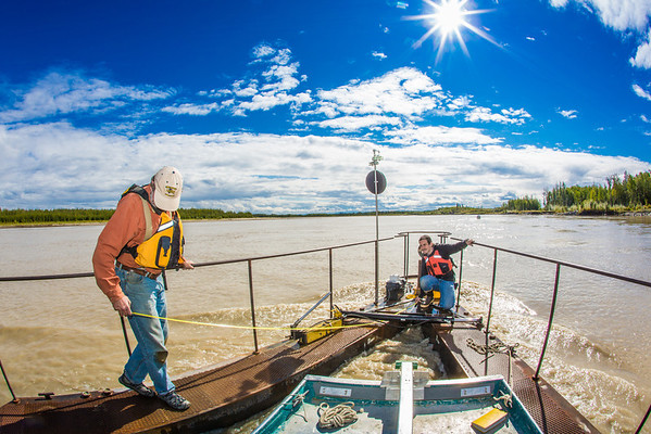 """Jack Schmid, left, and Paul Duvoy, research professionals with the Alaska Center for Energy and Power, take measurements on a prototype deployment boom on the Tanana River near Nenana. The pair are part of a team conducting research on the feasibility of using the river current to generate electricity for potential use throughout rural Alaska.  <div class=""""ss-paypal-button"""">Filename: AAR-12-3500-063.jpg</div><div class=""""ss-paypal-button-end"""" style=""""""""></div>"""