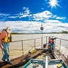"Jack Schmid, left, and Paul Duvoy, research professionals with the Alaska Center for Energy and Power, take measurements on a prototype deployment boom on the Tanana River near Nenana. The pair are part of a team conducting research on the feasibility of using the river current to generate electricity for potential use throughout rural Alaska.  <div class=""ss-paypal-button"">Filename: AAR-12-3500-063.jpg</div><div class=""ss-paypal-button-end"" style=""""></div>"