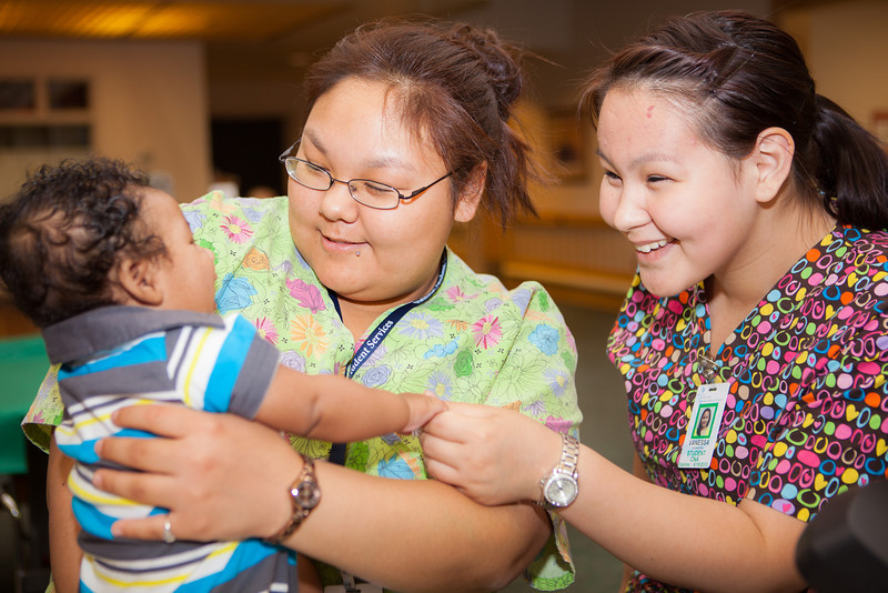 "Nurse Aid Training students Helen Pikonganna, left, and Vanessa Koonooka, from the UAF Northwest Campus interact with  a baby at the Denali Center in Fairbanks during their two-week clinical practicum.  <div class=""ss-paypal-button"">Filename: AAR-13-3859-107.jpg</div><div class=""ss-paypal-button-end"" style=""""></div>"