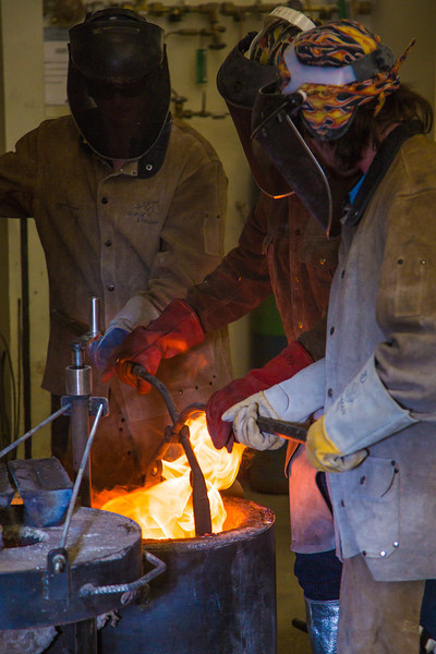 """Art major Joel Isaak, left, returns a pot of molten bronze into the furnace as part of the process of creating a life-sized sculpture for his senior thesis in the UAF Fine Arts complex.  <div class=""""ss-paypal-button"""">Filename: AAR-12-3347-112.jpg</div><div class=""""ss-paypal-button-end"""" style=""""""""></div>"""