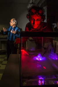 Physics major Michael Succone experiments with light from a laser as its being scattered by clouds of condensation inside an aquarium in a Reichardt Building lab.  Filename: AAR-13-4009-7.jpg