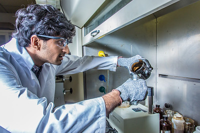 Graduate student Mukul Chavan pours a sample of heavy crude oil from the Kaparuk field on Alaska's North Slope. Chavan and other students in UAF's petroleum engineering program are using the samples to experiment with ways to recover more oil from existing fields.  Filename: AAR-13-3918-115.jpg