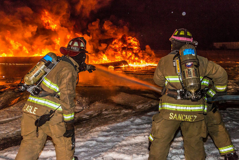 """Student firefighters with the University Fire Department spray water on a blaze of burning fuel during a live training drill at the Fairbanks International Airport.  <div class=""""ss-paypal-button"""">Filename: AAR-13-3995-173.jpg</div><div class=""""ss-paypal-button-end"""" style=""""""""></div>"""