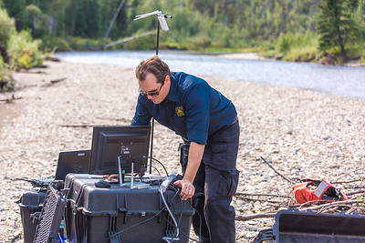 Trevor Parcell with the Alaska Center for Unmanned Aircraft Systems Integration (ACUASI) sets up a piloting station on a gravel bar along the upper Chena River. The UAV pilot was taking part in a joint effort with the U.S. Fish and Wildlife Service to collect video of important king salmon spawning habitat.  Filename: AAR-15-4593-127.jpg