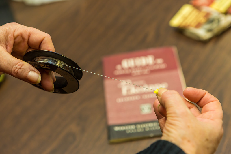 """Assistant Professor Leslie McCarthy holds a recording wire used with a device recently donated to the Oral History program at UAF's Rasmuson Library. The recorder used technology popular through the country in the 1930s-1960s.  <div class=""""ss-paypal-button"""">Filename: AAR-16-4783-06.jpg</div><div class=""""ss-paypal-button-end""""></div>"""