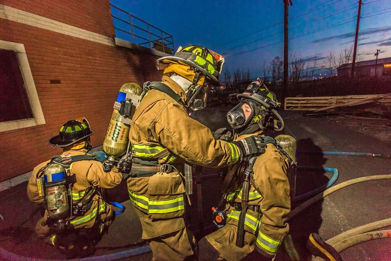 "Student firefighters Crosby Hanson (standing) and Ryan Sims check each others gear before entering a burning building as part of a UFD live training drill at the Fairbanks Fire Training Center.  <div class=""ss-paypal-button"">Filename: AAR-13-3978-39.jpg</div><div class=""ss-paypal-button-end"" style=""""></div>"