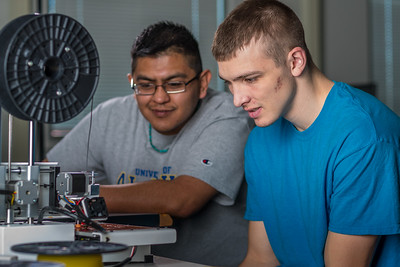 Seth Carstens, right, and Arch Chauhan watch the progress on their project during an open work session in UAF's Community and Technical College's 3-D print lab in downtown Fairbanks.  Filename: AAR-16-4857-050.jpg