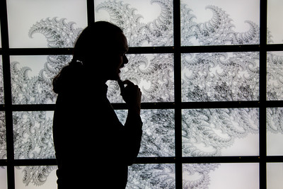 Assistant Professor Orion Lawlor stands in front of a random fractal design projected on the bioinformatics powerwall in the Chapman Building.  Filename: AAR-12-3272-111.jpg