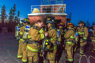Student fire fighters Spencer McLean, left, and John Jones prepare to enter a burning building as part of a live training drill at the Fairbanks Fire Training Center.  Filename: AAR-13-3978-30.jpg