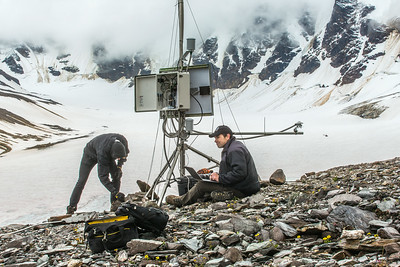 Joel Bailey, right, a research professional with UAF's Institute of Northern Engineering, downloads data from a weather station above the surface of the Jarvis Glacier in the eastern Alaska Range. At left, Ph.D. student Matvey Debolskiy helps stablize the station's foundation.  Filename: AAR-14-4256-319.jpg