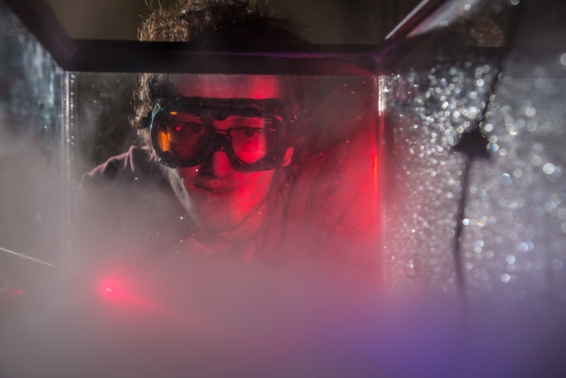 """Physics major Michael Succone experiments with light from a laser as its being scattered by clouds of condensation inside an aquarium in a Reichardt Building lab.  <div class=""""ss-paypal-button"""">Filename: AAR-13-4009-34.jpg</div><div class=""""ss-paypal-button-end"""" style=""""""""></div>"""
