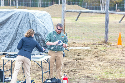 Pilot Mike Cook retreives the payload after the initial flight of the Aeryon Scout quadcopter at UAF's Large Animal Research Station.  Filename: AAR-14-4172-134.jpg