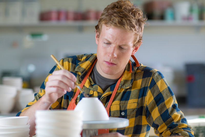 """Art major Ian Wilkinson works on one of the approximately 1,000 ceramic bowls needed for his senior thesis project in the fine arts complex on the Fairbanks campus.  <div class=""""ss-paypal-button"""">Filename: AAR-12-3547-112.jpg</div><div class=""""ss-paypal-button-end"""" style=""""""""></div>"""