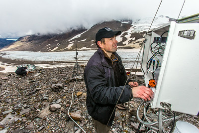 Joel Bailey, a research professional with UAF's Institute of Northern Engineering, works on a data collecting station above the surface of the Jarvis Glacier in the eastern Alaska Range.  Filename: AAR-14-4256-267.jpg