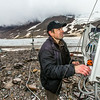 "Joel Bailey, a research professional with UAF's Institute of Northern Engineering, works on a data collecting station above the surface of the Jarvis Glacier in the eastern Alaska Range.  <div class=""ss-paypal-button"">Filename: AAR-14-4256-267.jpg</div><div class=""ss-paypal-button-end""></div>"