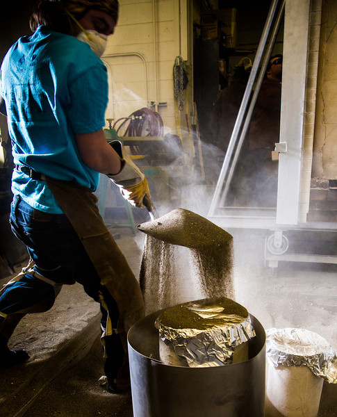 """Art major Bryson DeRonde shovels sand around plaster molds prior to a pouring of molten bronze as part of a senior thesis in the UAF Fine Arts complex.  <div class=""""ss-paypal-button"""">Filename: AAR-12-3347-011.jpg</div><div class=""""ss-paypal-button-end"""" style=""""""""></div>"""