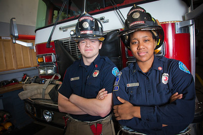 UAF student firefighters/EMTs John McGee and Lillian Hampton pose in front of one of the firetrucks housed in the Whitaker Building on the Fairbanks campus.  Filename: AAR-11-3223-132.jpg