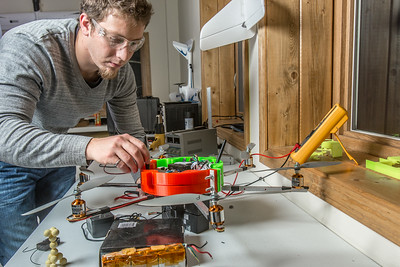 UAF graduate student Sam Vanderwaal checks the voltage of one of the connections on an unmanned aerial vehicle. The device is built primarly from plastic components generated from a 3-D printer housed in the south Fairbanks lab.  Filename: AAR-13-4026-206.jpg