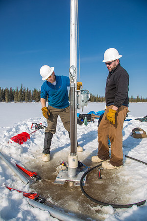 Associate Professor Mat Wooller, left, and Ph.D. candidate Jim Shobe test a new vibra-coring system through a hole in lake ice to sample long cores of sediment deep below the lake's bottom.  Filename: AAR-12-3346-074.jpg