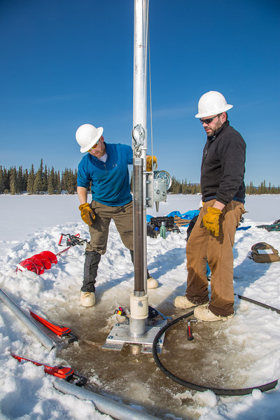 """Associate Professor Mat Wooller, left, and Ph.D. candidate Jim Shobe test a new vibra-coring system through a hole in lake ice to sample long cores of sediment deep below the lake's bottom.  <div class=""""ss-paypal-button"""">Filename: AAR-12-3346-074.jpg</div><div class=""""ss-paypal-button-end"""" style=""""""""></div>"""
