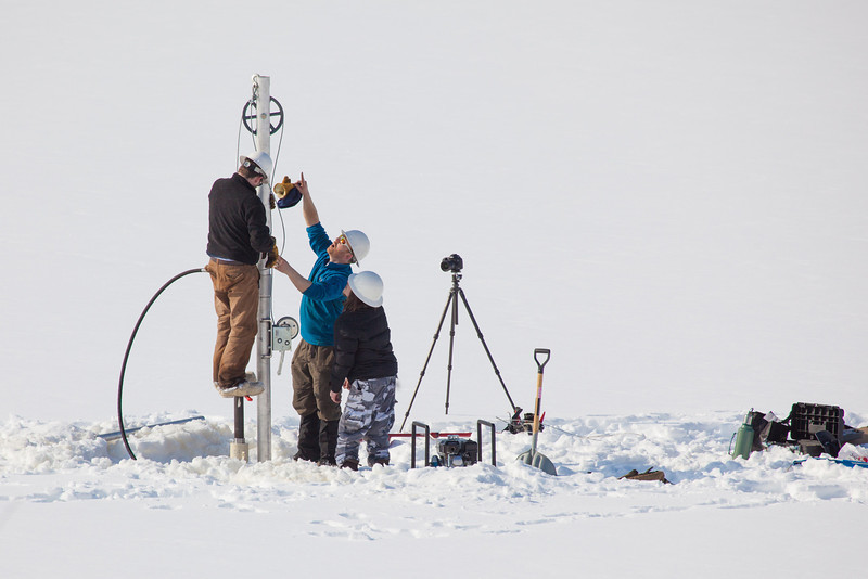 "Associate Professor Mat Wooller, blue shirt, and Ph.D. candidate Jim Shobe, left, test a new vibra-coring system through a hole in lake ice to sample long cores of sediment deep below the lake's bottom. Also helping is Terry Smith, right, a North Pole High School student intern.  <div class=""ss-paypal-button"">Filename: AAR-12-3346-020.jpg</div><div class=""ss-paypal-button-end"" style=""""></div>"