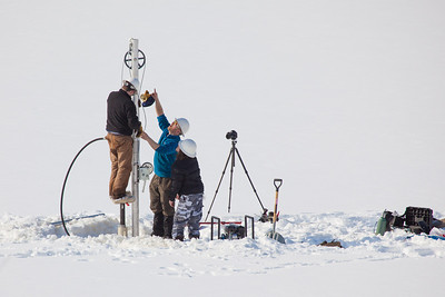 Associate Professor Mat Wooller, blue shirt, and Ph.D. candidate Jim Shobe, left, test a new vibra-coring system through a hole in lake ice to sample long cores of sediment deep below the lake's bottom. Also helping is Terry Smith, right, a North Pole High School student intern.  Filename: AAR-12-3346-020.jpg