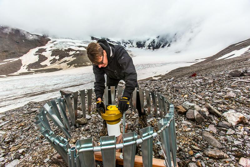 "Matvey Debolskiy, a Ph.D. student in geophysics, balances a precipitation gauge on a ridge above the Jarvis Glacier in the eastern Alaska Range.  <div class=""ss-paypal-button"">Filename: AAR-14-4256-299.jpg</div><div class=""ss-paypal-button-end""></div>"