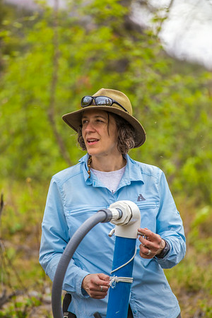 Associate professor Margaret Darrow, inspects a tube which extends deep into one of several frozen debris lobes which have appeared along the Dietrich River valley in the southern Brooks Range. Darrow, along with state geologists Ron Daanen, left, and Trent Hubbard, are trying to figure out how to slow down or stop the movement of the lobes which threaten the Dalton Highway and the nearby trans-Alaska pipeline.  Filename: AAR-14-4214-504.jpg