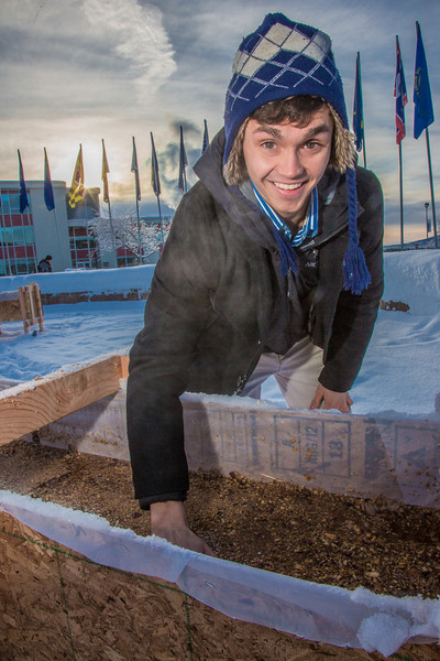 "Civil engineering major Ryan Williams-Cudo levels out sawdust mixed with water that when frozen, hardens into a substance many times stronger than concrete. Ryan led the group of student engineers on building the traditional ice arch on campus during the spring of 2013.  <div class=""ss-paypal-button"">Filename: AAR-13-3718-13.jpg</div><div class=""ss-paypal-button-end"" style=""""></div>"