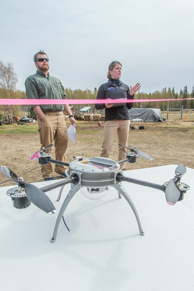 """Pilots Mike Cook, left, and Jennifer Haney, present a briefing for those assembled before the Aeryon Scout, similar to the one pictured here in front of them, took off on an historic flight May 5 at UAF's Large Animal Research Station.  <div class=""""ss-paypal-button"""">Filename: AAR-14-4172-23.jpg</div><div class=""""ss-paypal-button-end""""></div>"""
