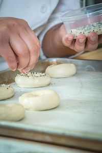 Charlotte Gordon applies onion and garlic and poppyseed to mini-bagels served during lunch at CTC's culinary arts kitchen in the Hutchison Center.  Filename: AAR-13-3811-123.jpg