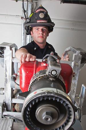 UAF student firefighter/EMT Ethan Stevenson checks some of the equipment aboard one of the firetrucks housed in the Whitaker Building on the Fairbanks campus.  Filename: AAR-11-3223-126.jpg