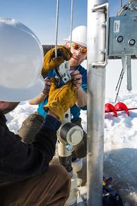Associate Professor Mat Wooller, blue shirt, and Ph.D. candidate Jim Shobe, left, test a new vibra-coring system through a hole in lake ice to sample long cores of sediment deep below the lake's bottom.  Filename: AAR-12-3346-034.jpg