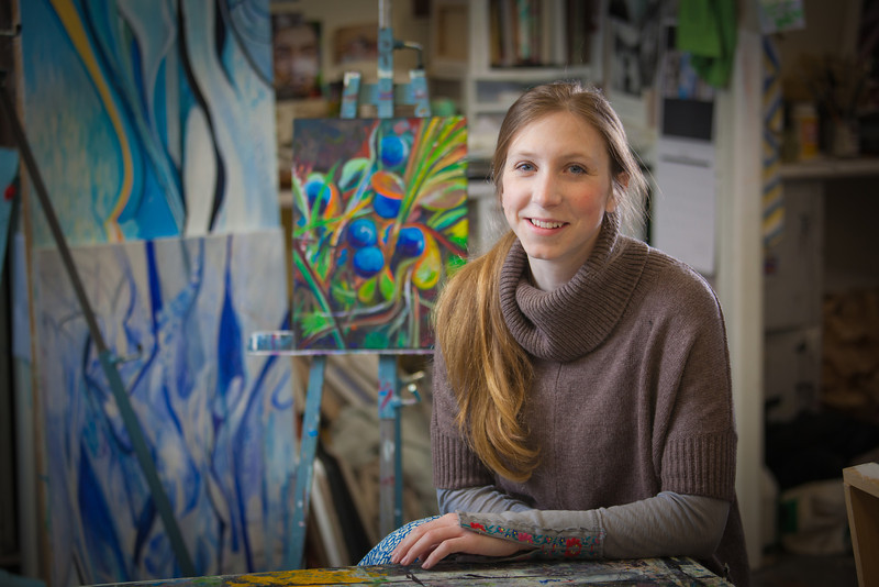 """Art major Klara Maisch poses in front of one of her paintings in the Fine Arts studio.  <div class=""""ss-paypal-button"""">Filename: AAR-12-3299-38.jpg</div><div class=""""ss-paypal-button-end"""" style=""""""""></div>"""