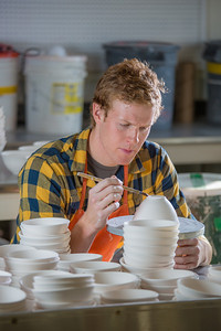 Art major Ian Wilkinson trims one of the approximately 1,000 ceramic bowls needed for his senior thesis project in the fine arts complex on the Fairbanks campus.  Filename: AAR-12-3547-090.jpg