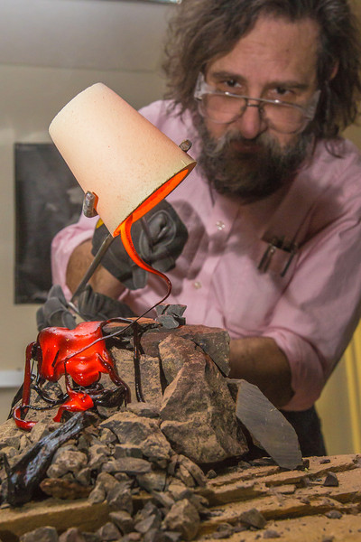 """Geology professor Rainer Newberry pours hot lava over volcanic basalt in a lab in the Reichardt Building on the Fairbanks campus.  <div class=""""ss-paypal-button"""">Filename: AAR-13-3730-57.jpg</div><div class=""""ss-paypal-button-end"""" style=""""""""></div>"""