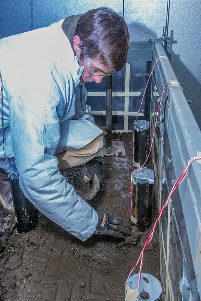 """Tom Polasek, a senior petroleum engineering major, works on constructing a simulated permafrost environment in a Duckering Building cold room. The project seeks to monitor the effects of heat from the wells and prevent the thawing of permafrost on Alaska's North Slope oil fields.  <div class=""""ss-paypal-button"""">Filename: AAR-14-4076-94.jpg</div><div class=""""ss-paypal-button-end""""></div>"""