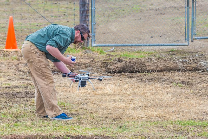 "Pilot Mike Cook retreives the payload after the initial flight of the Aeryon Scout quadcopter at UAF's Large Animal Research Station.  <div class=""ss-paypal-button"">Filename: AAR-14-4172-130.jpg</div><div class=""ss-paypal-button-end""></div>"