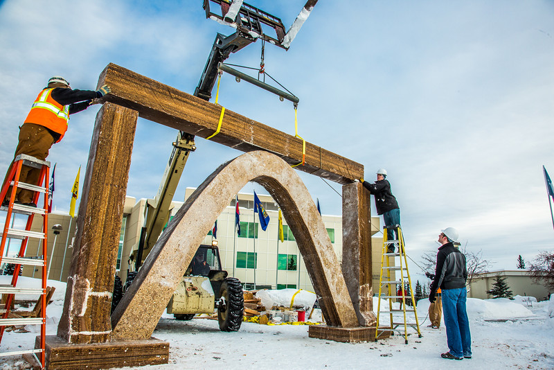 """Engineering students clear the bottom of one of the vertical supports as they raise the 2013 ice arch in Cornerstone Plaza on the Fairbanks campus. Students this year built the structure out of a mixture of ice and sawdust, which is many times stronger than concrete.  <div class=""""ss-paypal-button"""">Filename: AAR-13-3736-156.jpg</div><div class=""""ss-paypal-button-end"""" style=""""""""></div>"""
