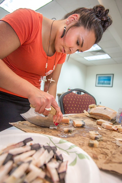 """Kelsey Wallace, a senior in UAF's rural development program from Bethel, chops muktuk before a potluck dinner hosted by students during a weeklong seminar on understanding the legislative process. Several state legislators and other officials attended the event at the Goldbelt Hotel in Juneau.  <div class=""""ss-paypal-button"""">Filename: AAR-14-4055-376.jpg</div><div class=""""ss-paypal-button-end"""" style=""""""""></div>"""