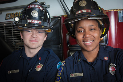 UAF student firefighters/EMTs John McGee and Lillian Hampton pose in front of one of the firetrucks housed in the Whitaker Building on the Fairbanks campus.  Filename: AAR-11-3223-134.jpg
