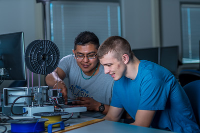 Seth Carstens, right, and Arch Chauhan watch the progress on their project during an open work session in UAF's Community and Technical College's 3-D print lab in downtown Fairbanks.  Filename: AAR-16-4857-057.jpg