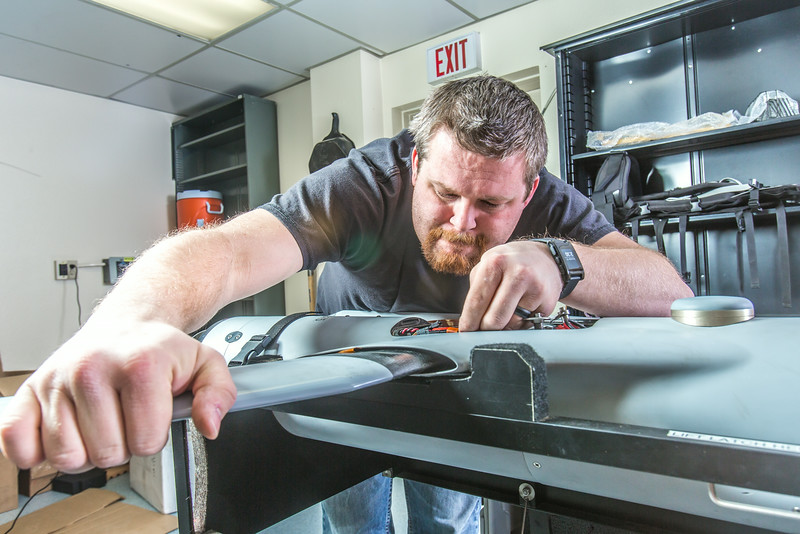 "Technician Michael Cook works on one of the unmanned aerial vehicles in UAF's Alaska Center for Unmanned Aircraft Systems Integration (ACUASI) shop in south Fairbanks.  <div class=""ss-paypal-button"">Filename: AAR-13-4026-142.jpg</div><div class=""ss-paypal-button-end""></div>"