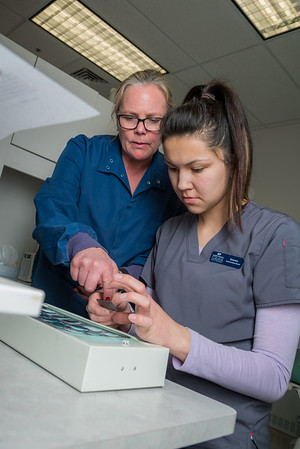 UAF Community and Technical College assistant professor Jenifer Filotei points out features on a radiograph x-ray with dental assisting student Vanessa Mountain at the school's facility on Barnette Street in downtown Fairbanks.  Filename: AAR-16-4873-001.jpg