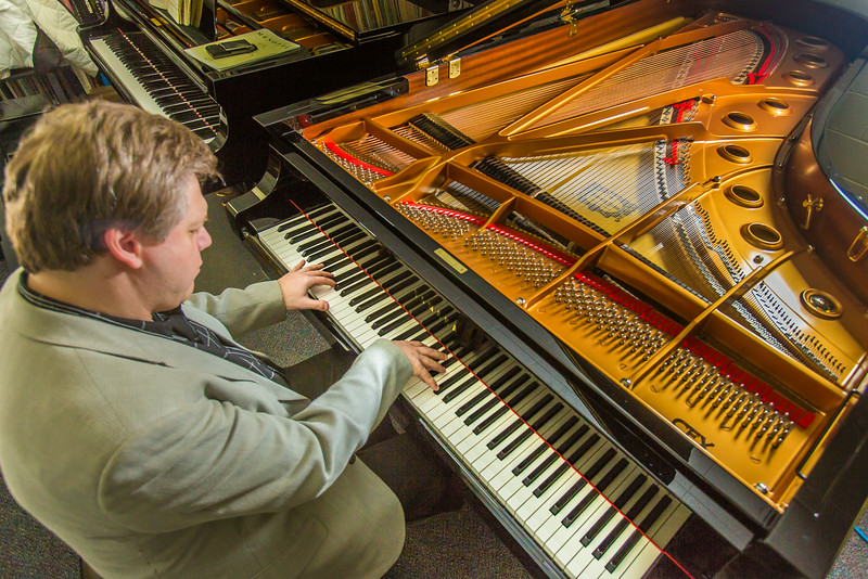 "UAF Professor Eduard Zilberkant plays on the Yamaha disklavier temporarily stored in his office. The instrument is being used in the summer of 2014 for the international piano e-competition hosted on the Fairbanks campus.  <div class=""ss-paypal-button"">Filename: AAR-14-4179-16.jpg</div><div class=""ss-paypal-button-end""></div>"