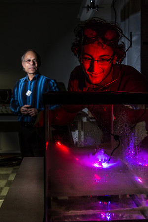 Physics major Michael Succone experiments with light from a laser as its being scattered by clouds of condensation inside an aquarium in a Reichardt Building lab.  Filename: AAR-13-4009-12.jpg