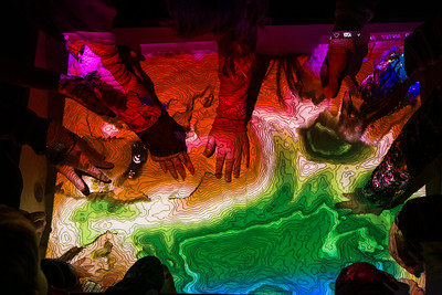 Children interact with an interactive topographic map during the Science Potpourri at the Reichardt  Building.  Filename: AAR-14-4141-123.jpg